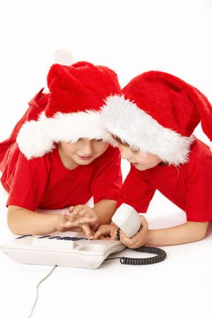 Two little boys in caps of santa dial a phone number, isolated   photo