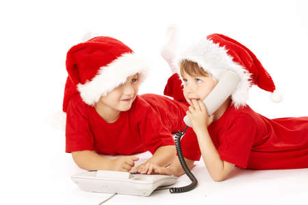 Two little boys in caps santa call by phone, isolated photo