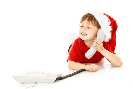 Little boy in a cap of santa calls by phone, isolated   photo