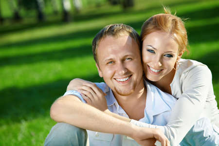 Laughing young couple embraces in a summer garden photo