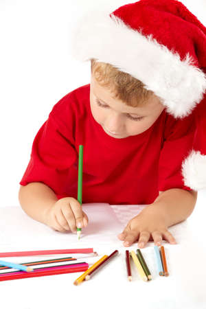 christmas list: Little boy in a suit of santa draws something, isolated Stock Photo