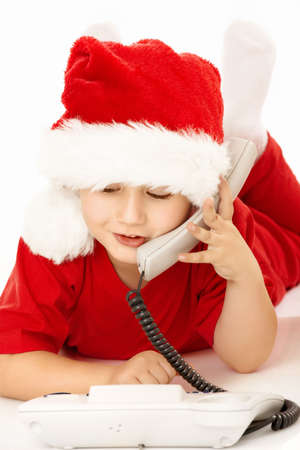 Little boy in a suit of santa lies and speaks on the phone, isolated   photo