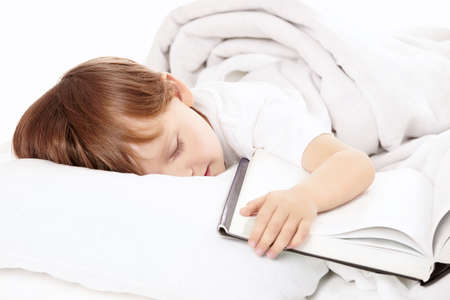 sleeps: Little boy sleeps in bed embracing the book, isolated