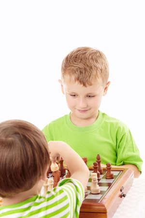 Two joyful little boys play chess, isolated   photo