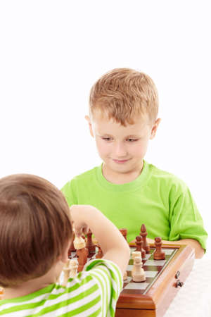 Two joyful little boys play chess, isolated   photo