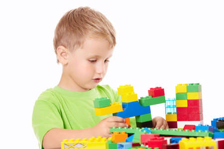 Little boy builds something of the plastic multi-coloured parts, isolated   photo