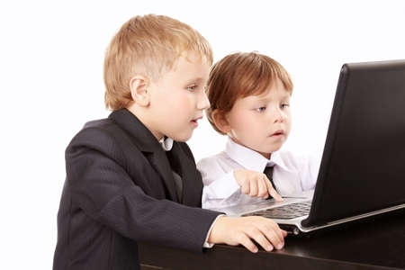 Two little boys in business suits together look in the screen of the laptop, isolated   photo