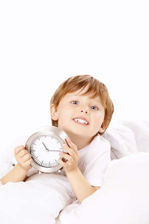 Little boy with an alarm clock in the bed, isolated photo