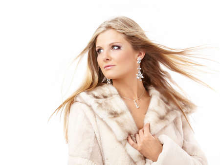 Portrait of attractive blonde in a fur coat, isolated