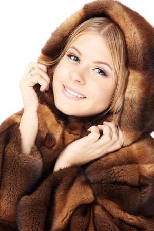 Beautiful blonde muffles up in the brown fur coat, isolated photo