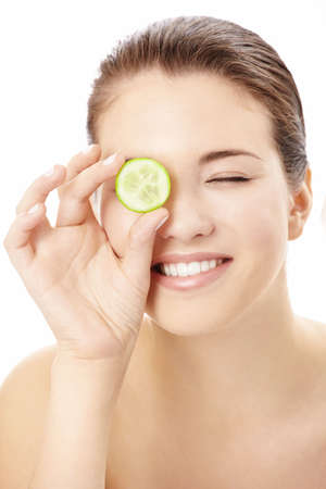 Portrait of the playful girl covering an eye by a slice of a cucumber, isolated photo