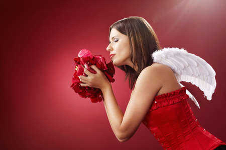Girl with angelic wings smells petals of the roses, isolated on a red background Stock Photo - 6163029