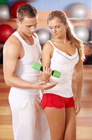 instructs: The trainer instructs the girl from dumbbells Stock Photo