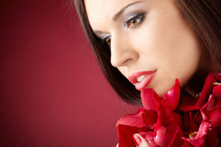Portrait of the charming girl with the red petals, isolated  photo