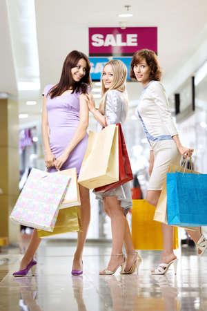 utmost: Three smiling elegant girlfriends to the utmost on shopping Stock Photo