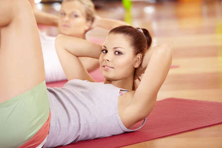 Happy girl does exercise for stomach muscles in sports club photo
