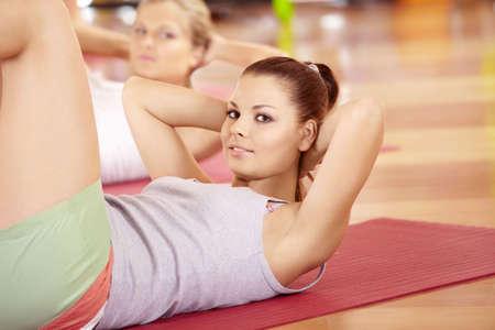 Niña feliz ejercicios para los músculos del estómago en el club deportivo Foto de archivo - 6230288