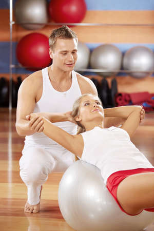 twisting: Twisting on fitball with support of the trainer