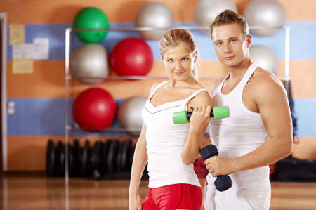 Pair of sportsmen with dumbbells in hands in sports club