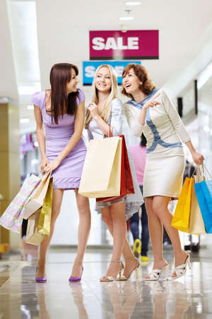 Three young women with bags laugh in shop  photo