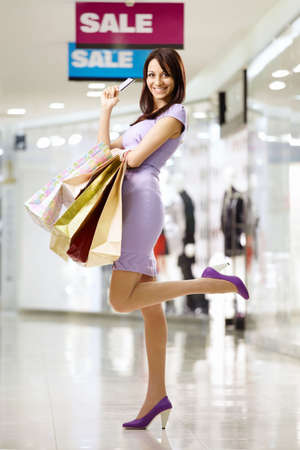 Beautiful girl smiles in shop, holding in a hand a credit card Stock Photo
