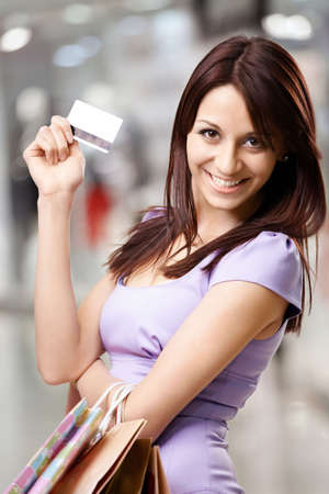 Portrait of the beautiful happy girl in the shop, holding in a hand a credit card photo