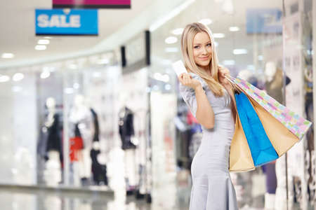 Attractive blonde with bags and a credit card in shop  photo