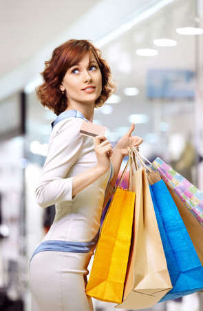 shopaholics: Happy curly woman on shopping with a credit card Stock Photo