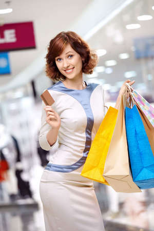 Young beautiful woman smiles in shop with bags and a credit card photo