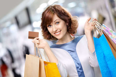 Portrait of the young beautiful woman smiling in shop with bags and a credit card photo