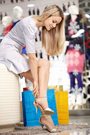 Attractive blonde tries on shoes in shop photo