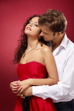 Guy embraces the girl behind on a red background photo