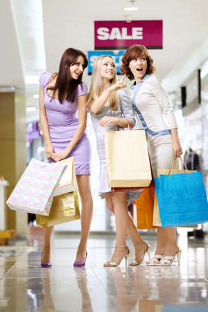 Three girl-friends to the utmost in shop show on something  photo