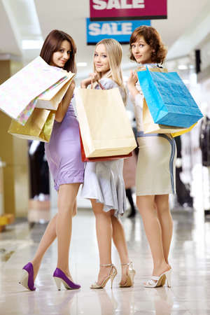 Three beautiful girlfriends in shop with bags photo