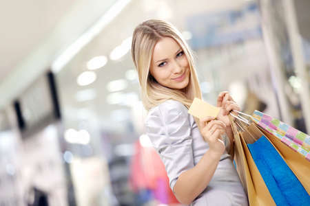 Portrait of the smiling blonde in shop with a credit card in a hand photo