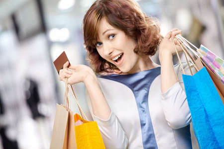shopping card: Portrait of the young beautiful woman smiling in shop with bags and a credit card