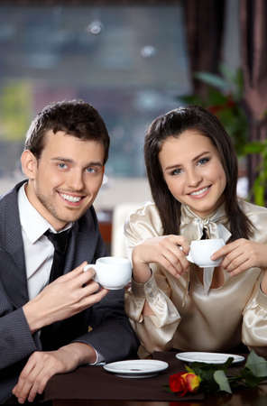 Happy smiling couple in cafe with cups in hands Stock Photo
