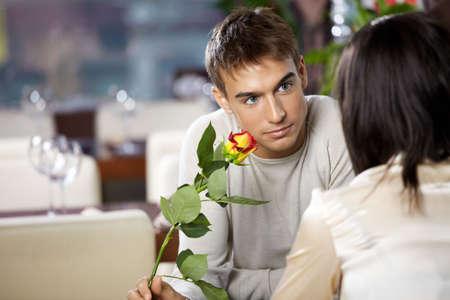 coquetear: Par en caf� - hombre da a la mujer una flor Foto de archivo