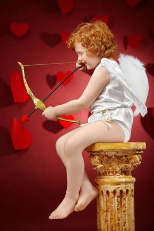 cupids: Profile of the small aiming boy - the cupid on a red background Stock Photo