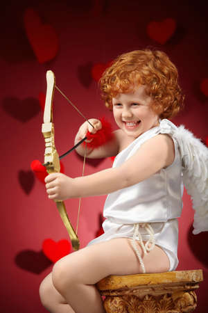 Laughing little boy in an image of the cupid does a shot photo