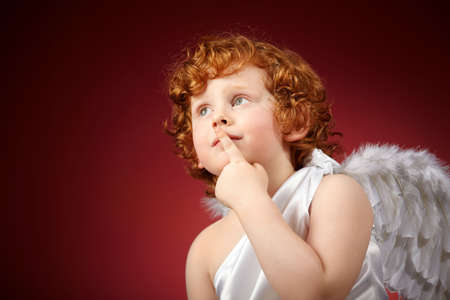 Portrait of the small thoughtful boy with wings behind the back on a red background photo