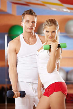 athleticism: Girl and the man with dumbbells in hands in sports club
