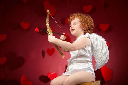Kleiner Junge in einem Bild von der Cupid auf einem roten Hintergrund
