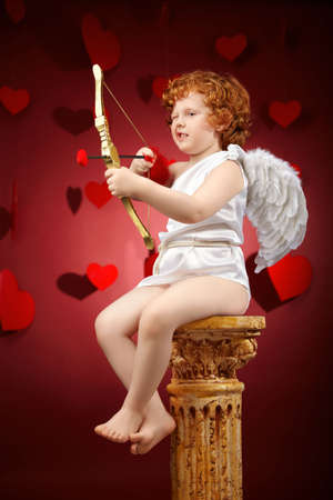 Small aiming boy in an image of the cupid on a red background photo