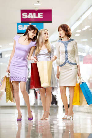 Three cheerful girl-friends with bags on walk in shop  photo