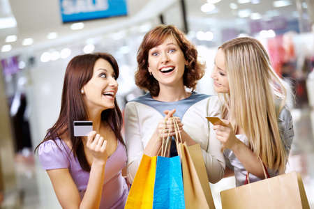 credit cards: Happy smiling girls with credit cards in shop