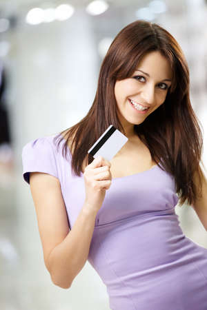 Portrait of the beautiful happy girl in the shop, holding in a hand a credit card Stock Photo - 6328145