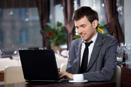 Business man with the laptop sits at a table in cafe photo