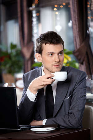 Business man with the laptop drinks coffee in cafe photo