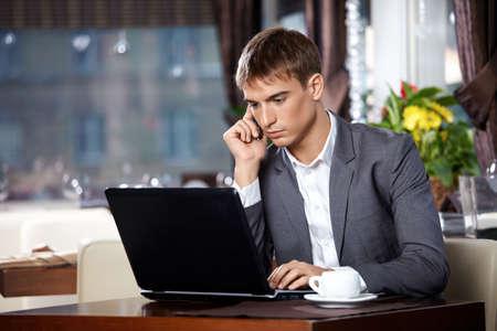 cafe internet: Hombre de negocios se comunica con el equipo port�til en m�vil en caf�